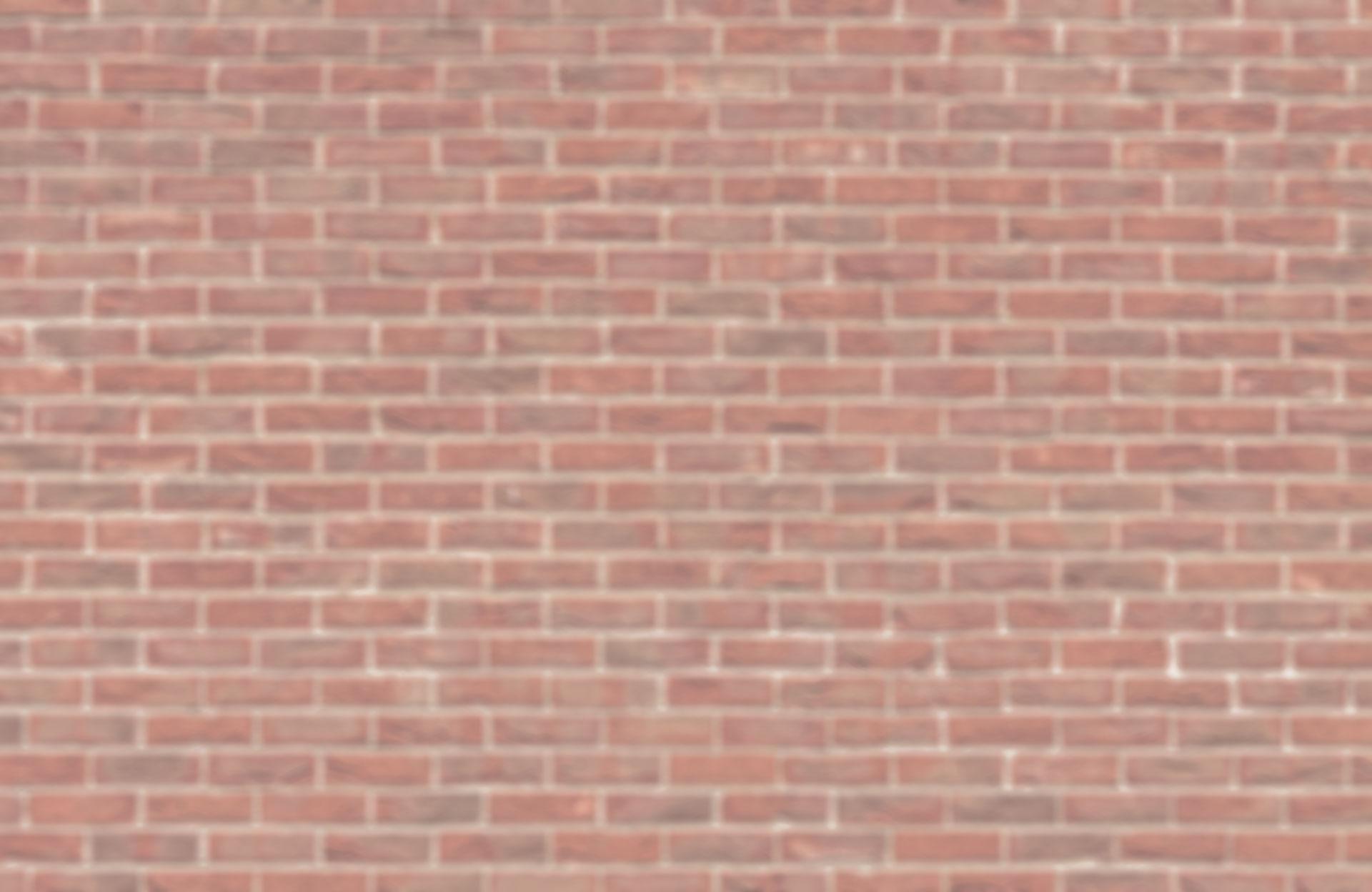 Photo d'un mur de brique pour arrière plan image d'équipe de la société Tout en couleurs (TEC), spécialiste en peinture électrostatique sur site